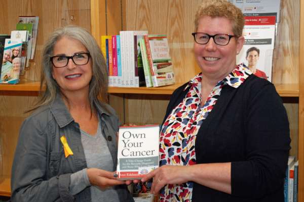 Two people holding a book in the cancer centre's resource centre