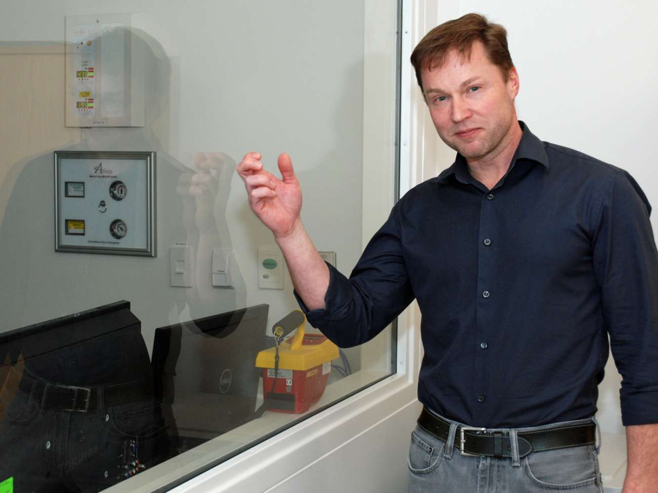 No ordinary glass: Medical physicist Andre Fleck shows the lead-infused glass separating the control and treatment rooms in the orthovoltage suite. Lead in glass, walls and doors keeps the risk of radiation exposure negligible.