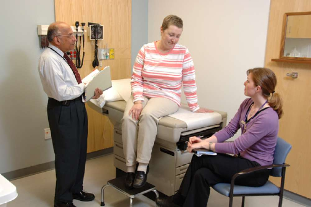 A photo of a patient and two care providers during an appointment