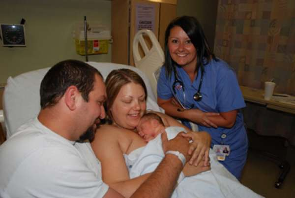 A photo of a nurse with a family and their new baby