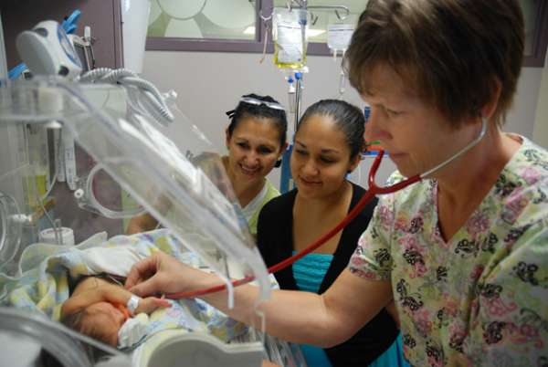 A photo of a family and a nurse in the NICU with a baby