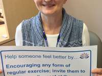 Maura's sign reads: Help someone feel better by encouraging any form of regular exercise; invite them to go for a walk, meet at the gym or attend a yoga classthumbnail image.