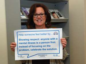 Sue's sign reads: help someone feel better by showing respect: anyone with a mental illness is a person first. Instead of focusing on the problem, celebrate the solution.