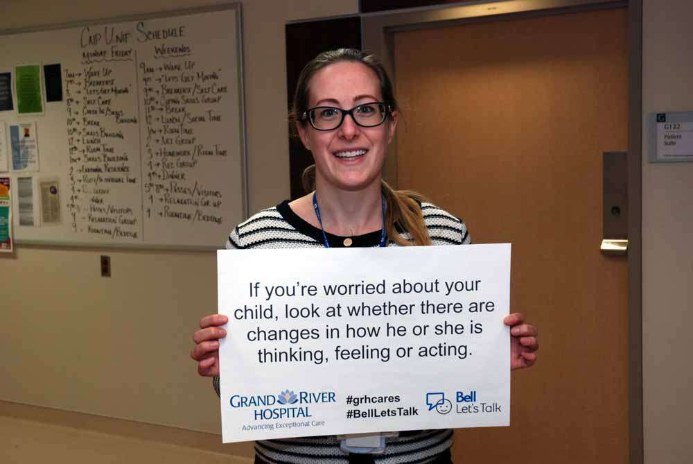 A care provider holding a sign reading: If you're worried about your child, look at whether there are changes in how he or she is thinking, feeling or acting.
