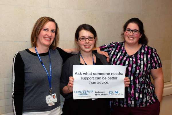 Three care providers holding a sign reading: ask what someone needs- support can be better than advice.