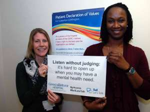Two staff holding a sign reading: Listen without judging: it's hard to open up when you may have a mental health need.