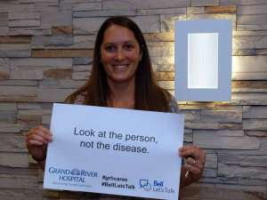 A staff member holding a sign reading: look at the person, not the disease