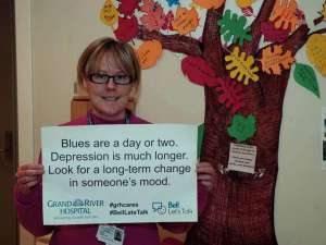 A care provider with a sign reading: Blues are a day or two. Depression is much longer. Look for a long-term change in someone's mood.