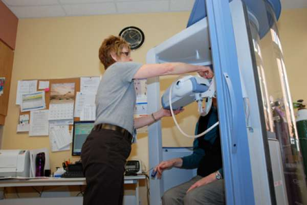 A care provider assisting a patient during a pulmonary function test