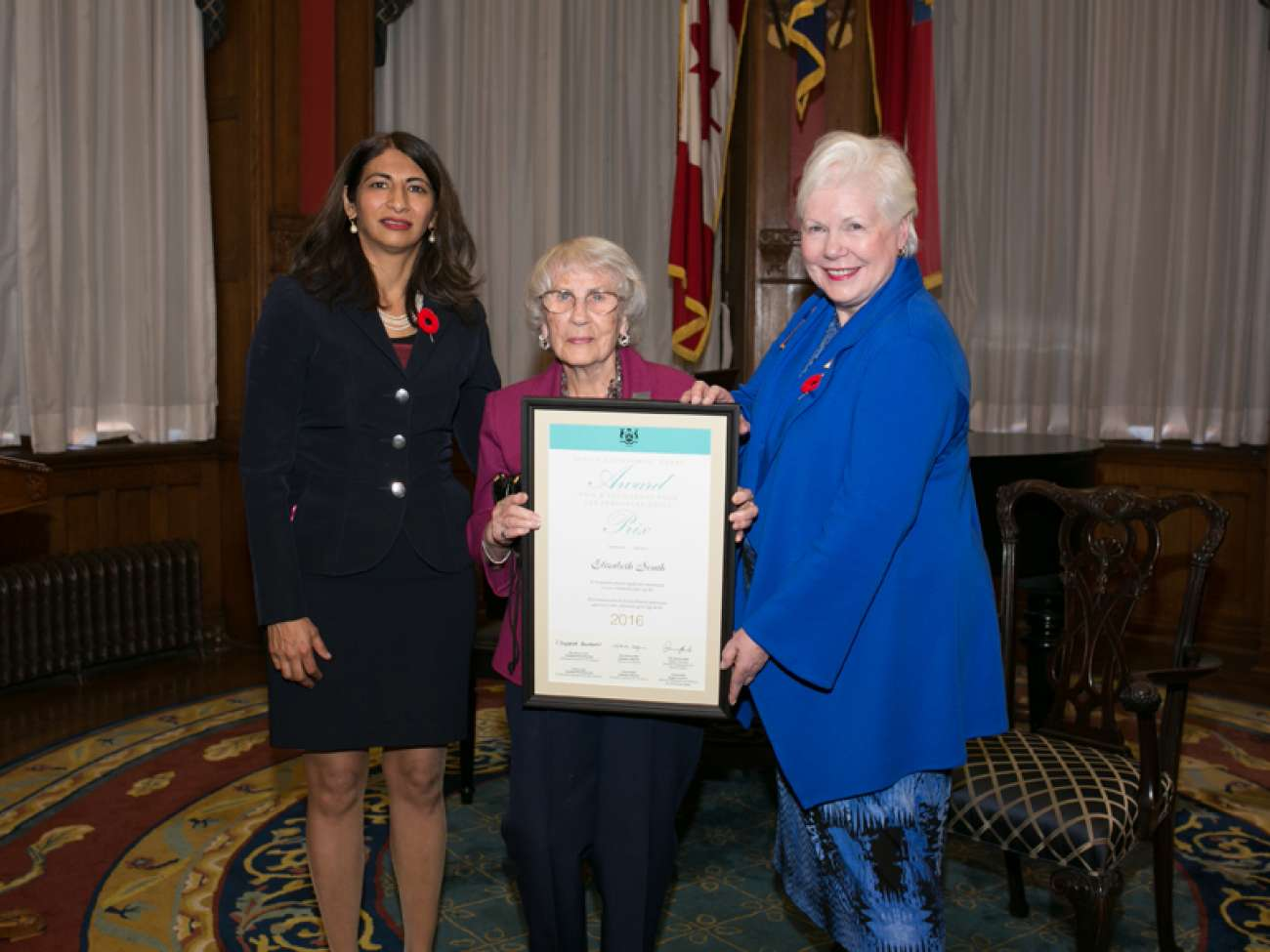 Betty South receives her award from the Hon. Dipika Damerla, Minister Responsible for Seniors Affairs (left) and the Hon. Elizabeth Dowdeswell, Lieutenant Governor of Ontario (right). Photo courtesy of the Government of Ontario.