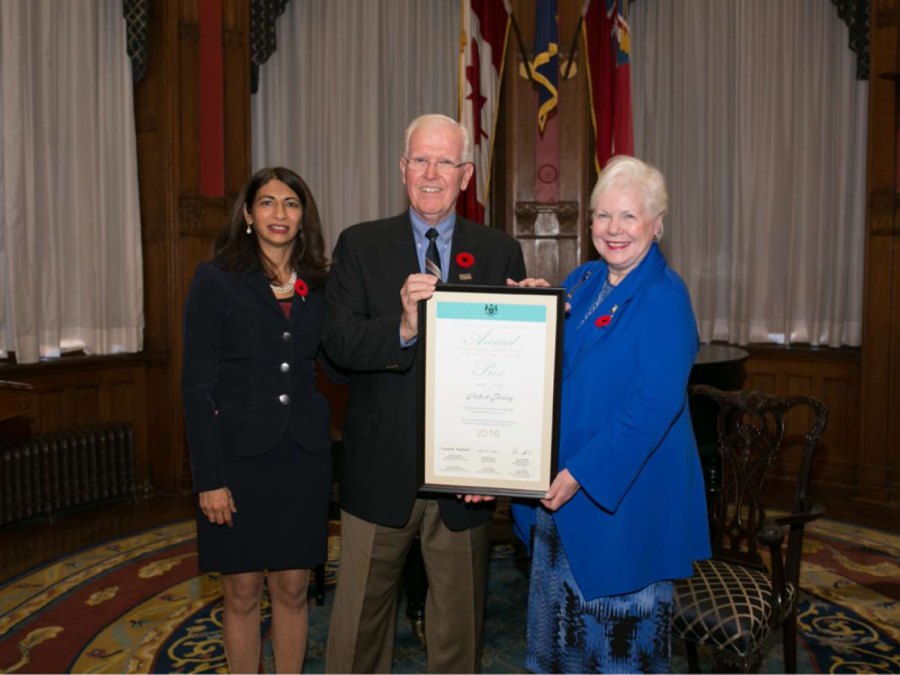 Robert Povey receives his award from the Hon. Dipika Damerla, Minister Responsible for Seniors Affairs (left) and the Hon. Elizabeth Dowdeswell, Lieutenant Governor of Ontario (right). Photo courtesy of the Government of Ontario.