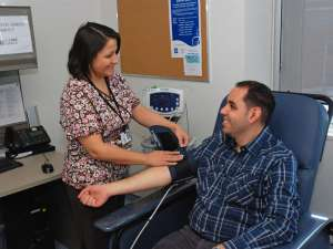A photo of a patient getting their blood pressure taken