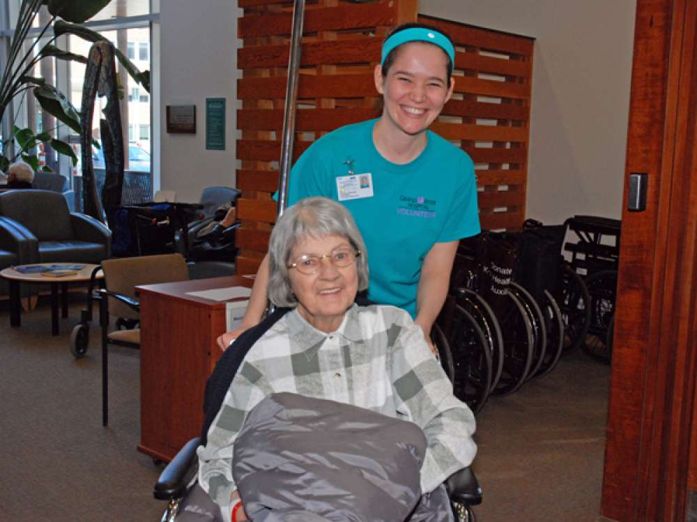 A photo of a volunteer pushing a patient in a wheel chair