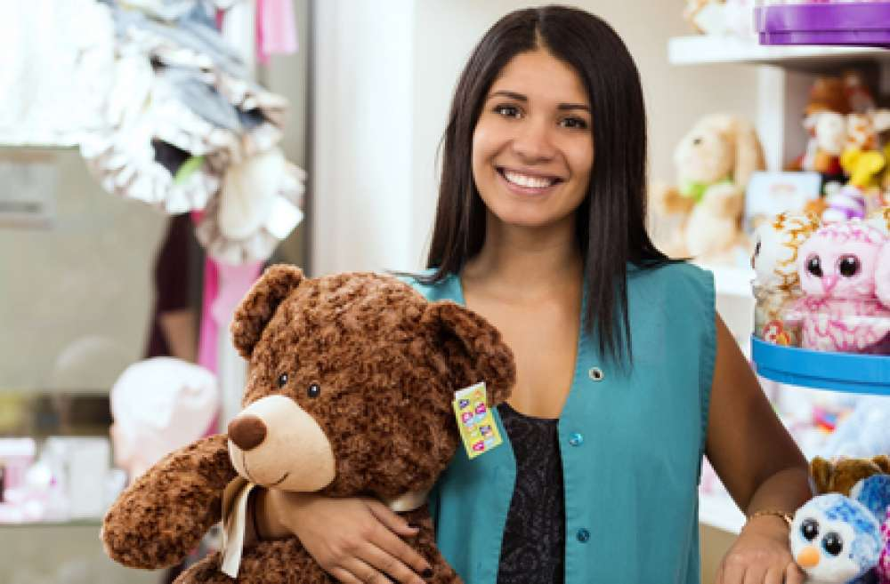 A photo of a volunteer holding a teddy bear
