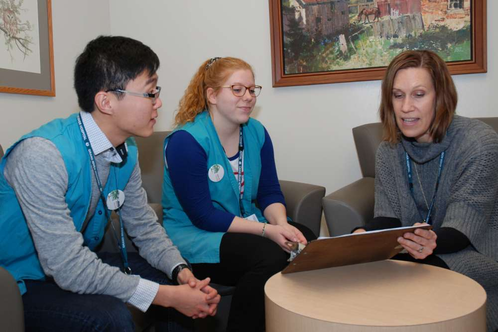 Marsha plans upcoming patient visits with volunteers Kunpei and Katie.