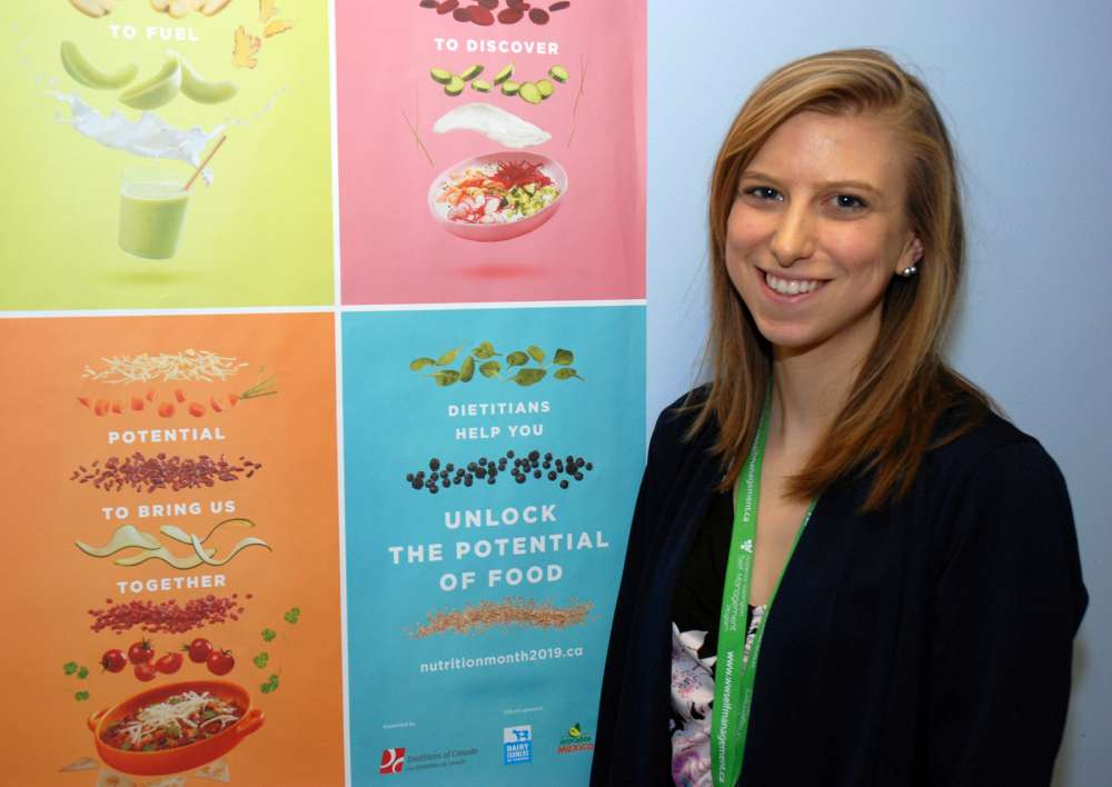 Melanie Thuss with a poster of food images