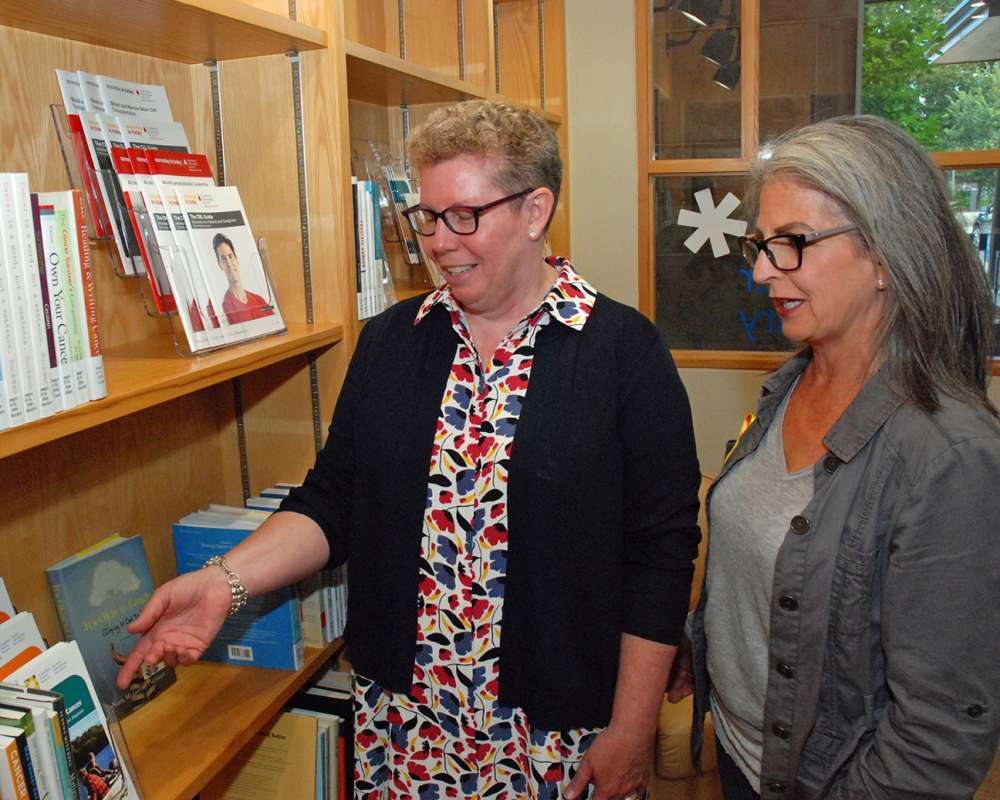 Two women looking at books instead the resource centre