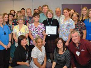Staff from environmental services and other leaders from the hospital congratulate Cindy Rogers on her award of excellence win.