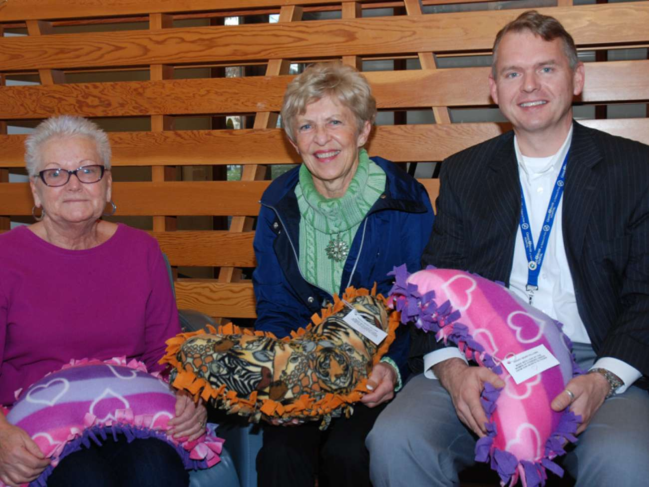 Shirley Chapman (centre) from the community of Foxboro Green drops off the latest donation of huggy pillows to patient Hildegard Anderson (left) and GRH's Owen Roszell (right)