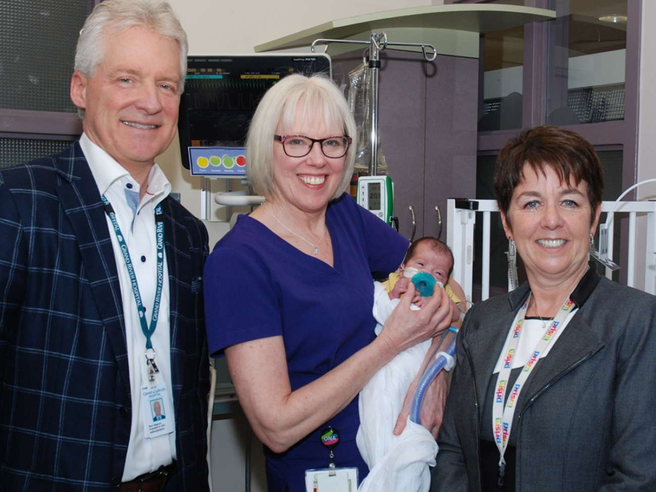 Brenda Menard stands with GRH CEO Ron Gagnon, VP Judy Linton and a young patient in the NICU